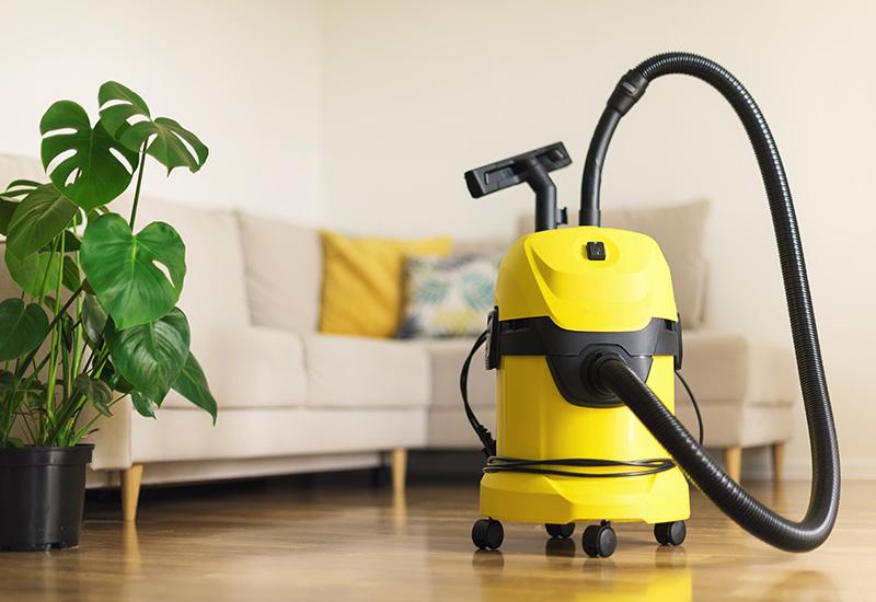 Aspiradora Moderno amarilla en la sala de estar. Espacio de copia. Concepto de aspiración de limpieza plana. Color verde.