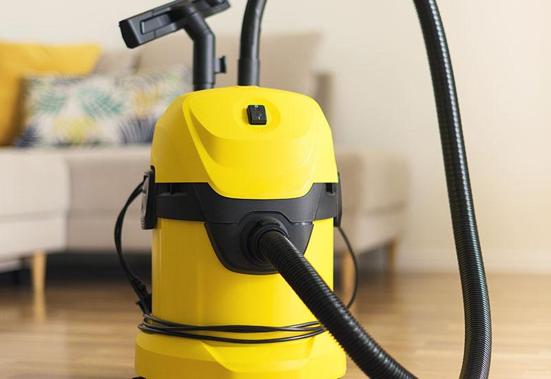 Aspiradora Moderno amarilla en la sala de estar. Espacio de copia. Concepto de aspiración de limpieza plana