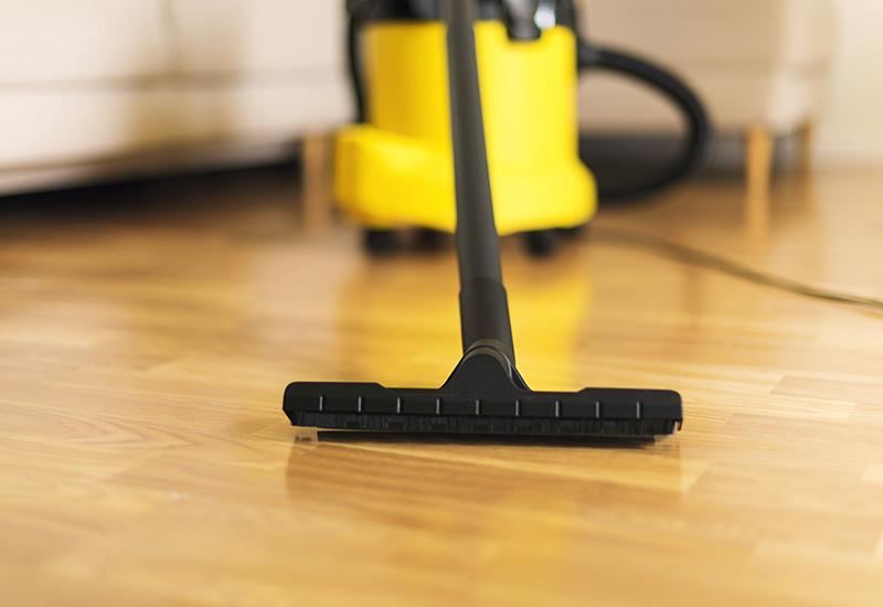 Mujer en guantes de protección limpiando la sala de estar con aspiradora amarilla. Espacio de copia. Limpio (2)