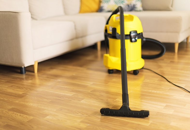Mujer en guantes de protección limpiando la sala de estar con aspiradora amarilla. Espacio de copia. Limpio