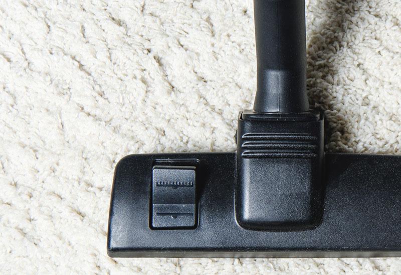 vista superior de alfombra blanca y aspiradora, vista de cerca